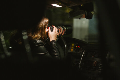Young woman taking pictures with a camera out of a car at night - LJF00110