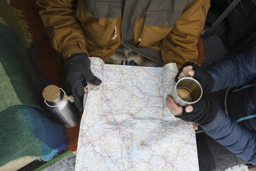 Couple with hot drink and winter clothing studying road map - PSIF00283