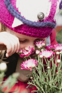 Close-up of girl smelling at flowers - PSIF00295