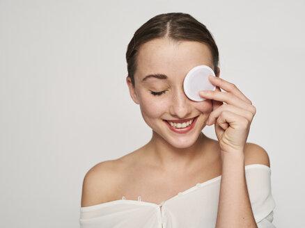 Beauty Portrait, junge lachende Frau mit Make-up Pad vor Auge Studio, München, Deutschland - PNEF01540