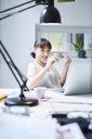 Portrait of smiling young businesswoman sitting at desk in an office - PNEF01549
