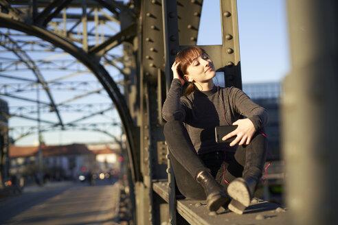 lächelnde junge Frau mit Smartphone in urbaner Umgebung auf Brücke sitzend München, Bayern, Deutschland - PNEF01564