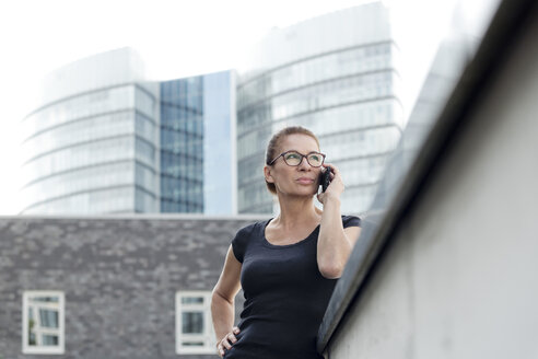 Woman on cell phone in front of office building - FLLF00226