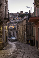 View from an alley in Ragusa Ibla to Ragusa Superiore at dusk, Ragusa, Sicily, Italy - MAMF00763