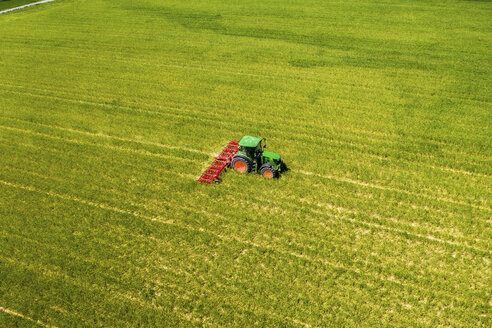 Aerial view of tractor on field, soil loosening, Hochtaunuskreis, Hesse, Germany - AMF07073