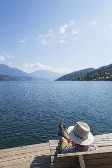 Man resting at lakeshore, Seeboden, Millstatt Lake, Carinthia, Austria - GWF06098