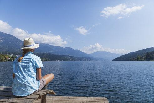 Woman resting at lakeshore, Seeboden, Millstatt Lake, Carinthia, Austria - GWF06101
