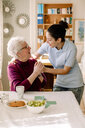 Smiling retired senior woman holding hands of young female volunteer while talking in nursing home - MASF12362