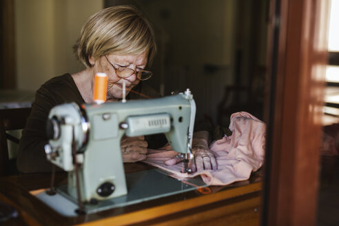 Senior woman using an sewing old machine at home - LJF00114