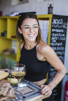 Portrait of smiling woman having a drink at a bar - LJF00120