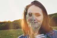 Portrait of smiling teenage girl with grasses at sunset - ANHF00108