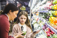 Mother showing cucumber to daughter while grocery shopping in supermarket - MASF12432