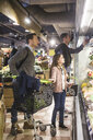 Father and daughter looking for fresh vegetables on shelves in grocery store - MASF12435