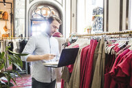 Confident male entrepreneur using laptop while standing by clothes rack in boutique - MASF12447