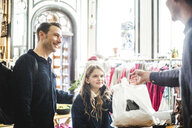 Family receiving shopping bag from salesman at checkout counter in boutique - MASF12456