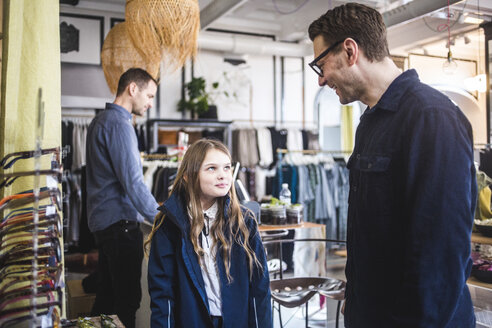 Smiling father wearing eyeglasses while looking at cute daughter in boutique - MASF12462