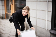 Female real estate agent looking away while arranging blank signboard on sidewalk - MASF12471