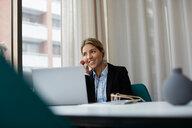 Smiling realtor talking through headphones while using laptop at estate office - MASF12480