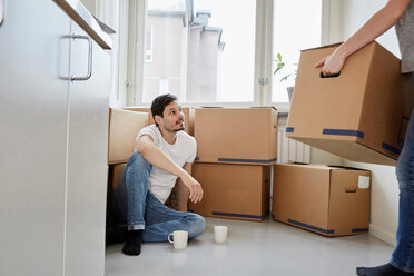 Man with coffee mugs looking at woman carrying cardboard boxes in new house - MASF12510