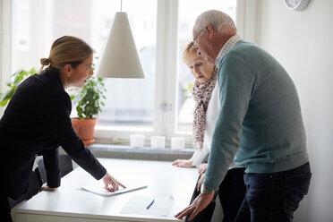 Realtor explaining documents of new house to senior couple - MASF12519