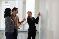 Real estate agent showing color samples to couple in new home - MASF12522
