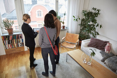 High angle view of real estate agent showing digital tablet to couple at home - MASF12534