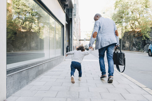 Rear view of father and daughter walking on sidewalk in city - MASF12549