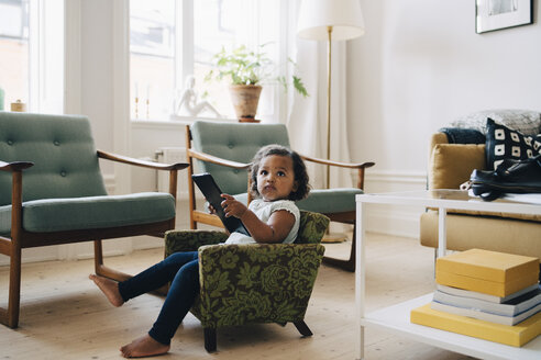 Full length of girl holding digital tablet while sitting on small armchair at home - MASF12555