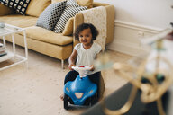 High angle view of girl riding toy car in living room at home - MASF12570