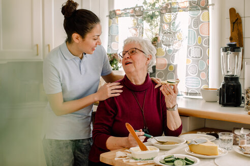 Retired senior woman eating breakfast while talking with female volunteer at nursing home - MASF12591