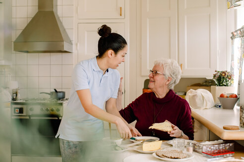 Smiling retired elderly woman talking with female caregiver in kitchen at nursing home - MASF12594