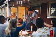 Man and woman kissing during dinner party with friends - MASF12624