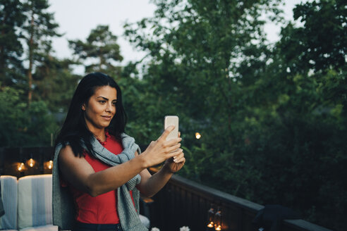 Smiling mid adult woman taking selfie in balcony during sunset - MASF12630