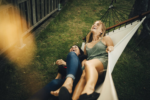 High angle view of cheerful female friends with lying on hammock at yard - MASF12648
