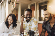 Cheerful friends having fun at dining table during dinner party - MASF12660