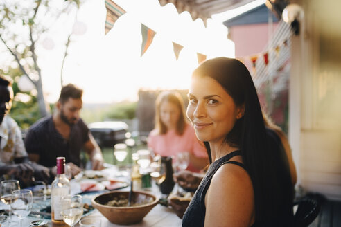 Portrait of smiling woman enjoying dinner party with friends at back yard - MASF12663