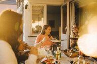 Happy friends enjoying food at dining table in dinner party - MASF12669