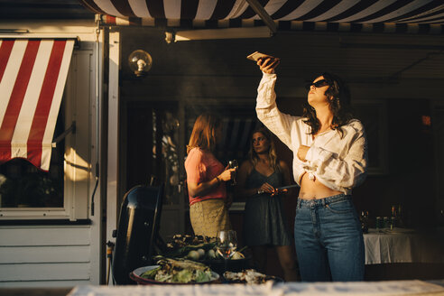 Woman photographing food on barbecue grill through smart phone while friends standing in background - MASF12672