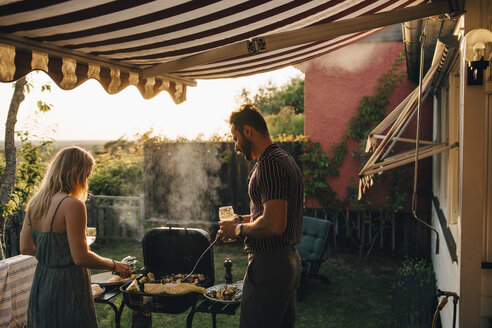 Male and female friends grilling food while having wine in party - MASF12678