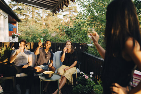 Friends raising toast while enjoying drinks in party at back yard - MASF12681