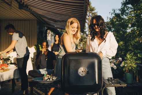 Female friends talking while grilling food on barbecue in dinner party - MASF12684