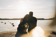 Rear view of romantic couple sitting on jetty against lake during summer - MASF12699