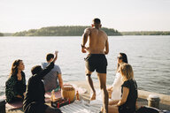Friends looking at shirtless man diving from jetty at lake against sky - MASF12708