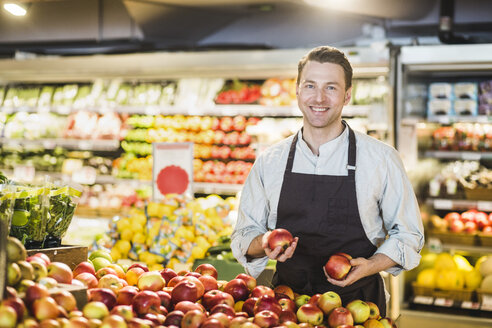 Portrait of smiling mature owner standing at apple stall in grocery store - MASF12750