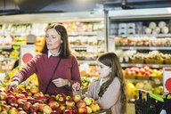 Mother and daughter choosing fresh apples at market stall - MASF12756
