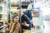 Father and daughter looking at mobile phone while crouching by refrigerator in store - MASF12768