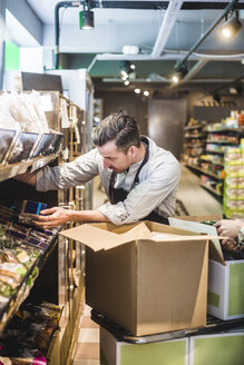 Salesman unloading cardboard box while arranging packets on shelf in store - MASF12774