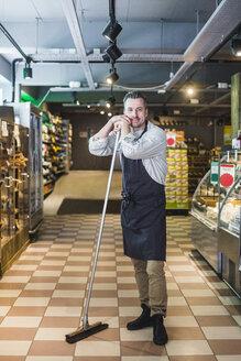 Full length portrait of smiling mature entrepreneur holding broom while standing in store - MASF12780