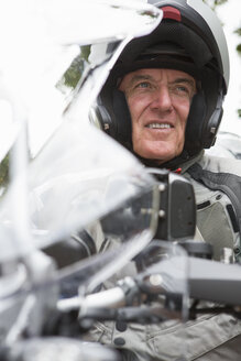 Close up of smiling senior man wearing helmet on motorcycle - JUIF01267