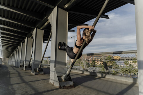 Sporty woman working out o a bridge, leaning on bar - ERRF01478